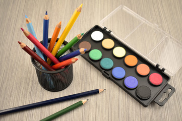 Watercolor tool stock images. Back to school border. Art supplies on a wooden background. School supplies for painting
