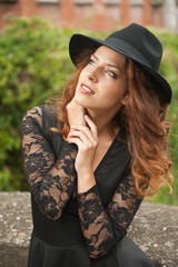 Charming young light brown hair brunette woman with big black hat and blouse with lace sleeves. Sexy gorgeous young woman with curly hair posing. Beautiful portrait of a sensual woman with long hair