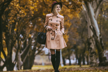 Mature woman walks in the autumn park