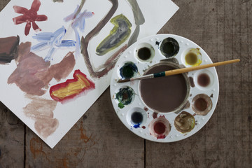 Finished paintings on wooden boards have a palette and a puddle placed on top by children.
