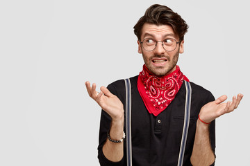 Indoor shot of handsome hesitant guy shrugs shoulders, looks doubtfully aside, doesn`t know what to say, wears stylish black shirt and red bandana on neck, stands over white wall with copy space