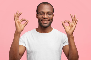 Okay, I will deal with it! Happy African American middle aged male with broad toothy smile, shows ok gesture, closes eyes in pleasure, dressed casually, isolated on pink background, approves something
