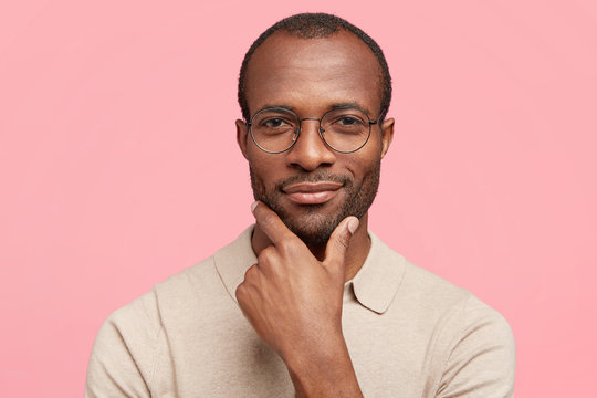 Headshot of serious dark skinned male boss holds chin, contemplates about succeessful agreement, looks mysteriously at camera, dressed in casual t shirt, stands indoor against pink background