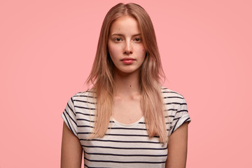 Horizontal shot of pretty Caucasian female with serious expression, healthy skin, light hair, dressed in striped t shirt, poses over pink background has appealing appearance. Student thinks about exam