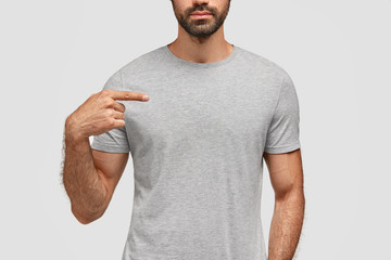 Cropped image of bearded guy points at his new t shirt, shows space for your designing content or advertisement. Muscular man wears casual grey cotton clothes, isolated over white background