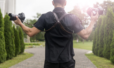Professional wedding photographer in black shirt and with shoulder straps holding cameras like a guns against the green garden. Wedding photography.