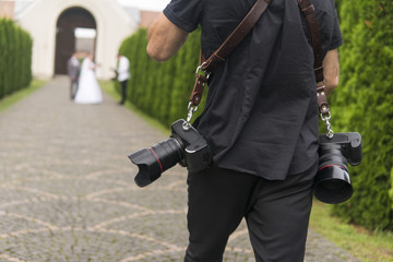 Professional wedding photographer takes pictures of the bride and groom in garden, the photographer in action with two cameras on a shoulder straps.