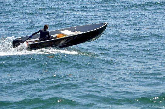 Small black aluminum motor boat primarily used for fishing.
