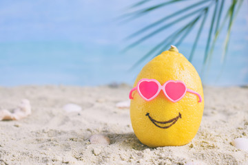 Creative minimal summer idea. Lemon citrus hipster in sunglasses on sand. Tropical beach concept. Creative art. Copy space
