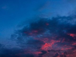 Dark blue sky with violet and red clouds