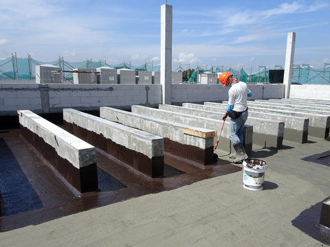Waterproofing layer applied by construction workers on top of concrete slab. Waterproofing layer to prevent water from entering below of the concrete slab.