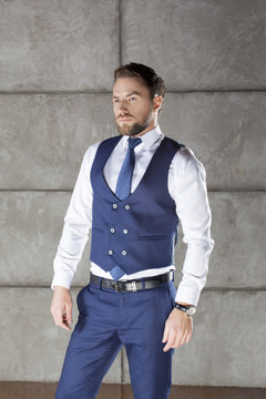 Handsome man wearing blue vest suit and tie. Perfect hair style and beard