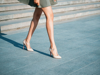 Sexy legs with high beige heels shoes on stone stairs of city. Business woman walking on boulvard alone. Attractive girl in short dress at summer season.