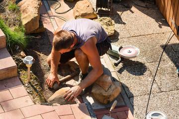 Man building a sandstone wall