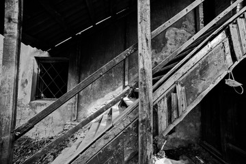 Black and white photo of a wooden staircase of an abandoned house