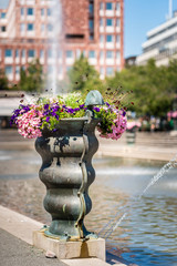 Selective focus of a large bronze vase with colorful flowers at a city square with water fountain and buildings in the background.
