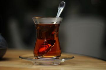 Glass cup of black tea, teaspoon on wooden table