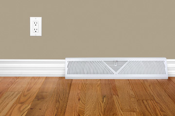 Bedroom wall with heating register, electrical outlet and hardwood floor