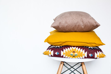 Cushions on the chair white wooden background close up with copy space. Sweet home and cozy concept