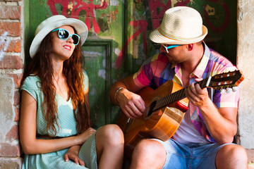 Happy smiling couple in sunglass and hat  with guitar drinking juice spending carefree time together.