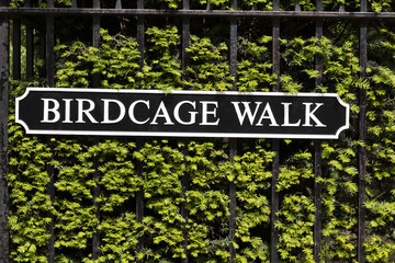 Birdcage walk sign on rusted steel fence with green foliage behind