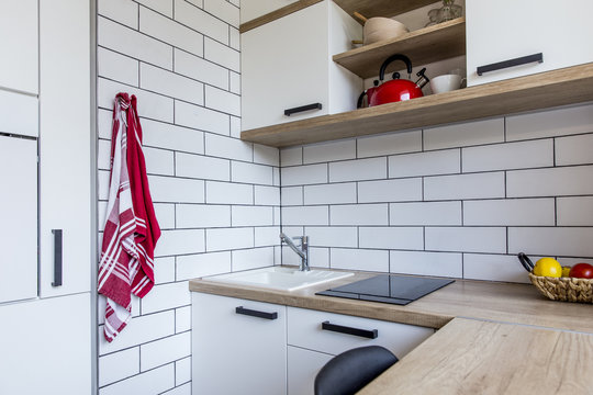 Small tiny white kitchen in panel house in the Czech Republic after the reconstruction with white brick wall and red and oak decoration and oak floor