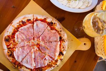 Italian food dinner. Pizza with tomato prosciutto mozzarella glass white wine summer outdoor restaurant