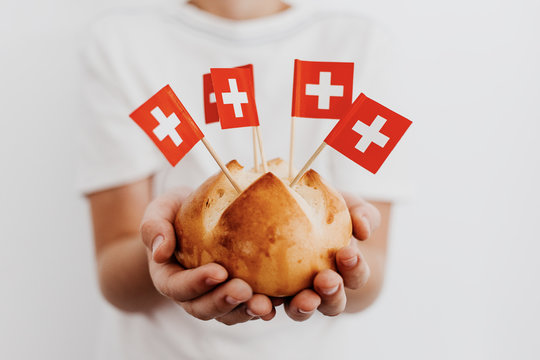 Traditional swiss bread buns called in German 1.Augustweggen baked in Switzerland to celebrate Swiss National Day on August 1st. Body parts, children hands holding bread.