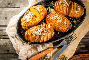 American traditional home cooking. The vegan diet. Homemade Hasselback Potato with Fresh Herbs and cheese. On old wooden table, copy space