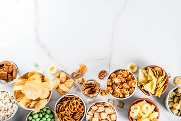 Variation different unhealthy snacks crackers, sweet salted popcorn, tortillas, nuts, straws, bretsels, white marble background copy spaceealthy snacks
