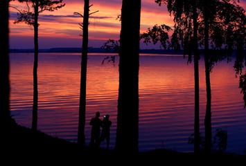 People take photos during sunset over the lake near the village Sosenka