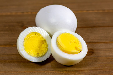 Hardboiled eggs with one cut in half on a plate at the kitchen table