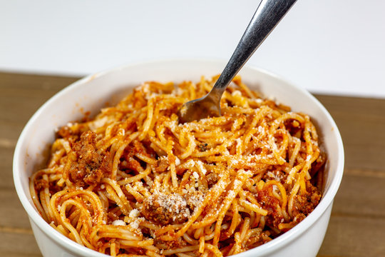 Spaghetti Bolognese in a deep white bowl on the wooden kitchen table waiting to be eaten