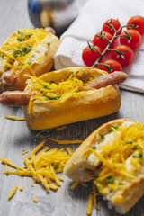 Snack, fast food, hot dogs with Bavarian sausages and grated cheddar on the wooden tray. Travel food concept.
