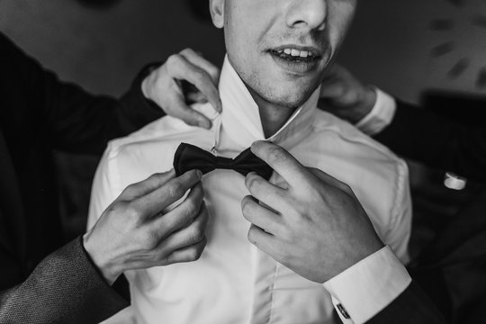 Groom getting ready in the morning with groomsmen in the room. man hands putting on jacket and bow tie, standing at window light in hotel. preparation for wedding day