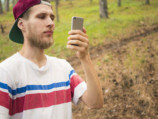 close young bearded man taking a photo with phone walking in the switzerland pine forest