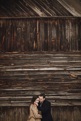 gorgeous bride in coat and stylish groom hugging at wooden house. wedding couple gently hugging and embracing in snowy park. barn wedding. romantic sensual moment of newlyweds