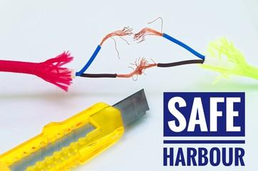 Bunte Kabel die getrennt und notdürftig geflickt wurden und einem Cuttermesser mit Aufschrift Safe Harbour