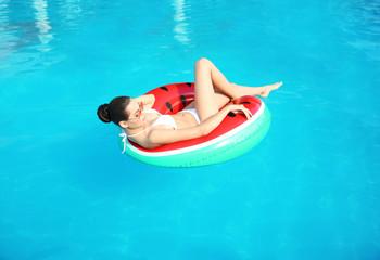 Beautiful young woman wearing bikini on inflatable ring in swimming pool
