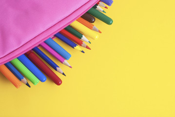 Colored Pencils school supplies in pink case yellow background. Back to School. Copy space for Text.