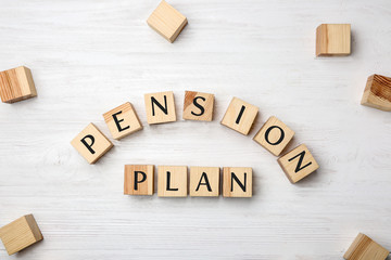 Cubes with text PENSION PLAN on white wooden background