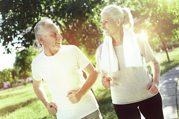 Energetic pensioners. Happy energetic elderly couple spending time together while running in a beautiful park