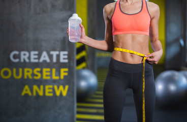 Shredded lady is demonstrating abdomen while standing in gym. She is checking changes by estimating belly size with centimeter tape. She is wearing sport clothes and holding sport bottle of water in