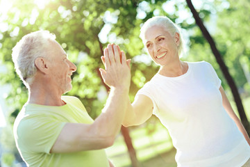 Giving five. Happy cheerful positive aged man giving five to his kind smiling wife while being outside