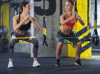 Smiling shapely ladies are training with latex band in gym. Two girls are doing sit-ups and looking at each other with joy. They are wearing sport clothes and trainers while enjoying joint effort