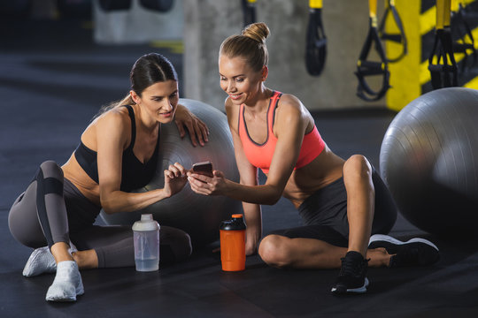 Smiling fit lady is showing her female friend something on phone. Both girls are resting after training together in sport center. They are sitting on floor and leaning on fitness balls during
