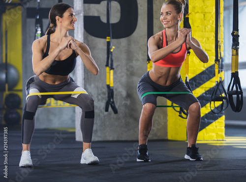 2546975ea0b Smiling shapely ladies are training with latex band in gym. Two girls are doing  sit-ups and looking at each other with joy. They are wearing sport clothes  ...