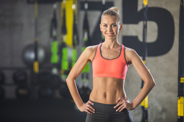 Waist up portrait of cheerful athletic woman. Ripped girl is standing in fitness center and grinning while looking at camera. Female is wearing sport clothes and keeping hands on waist