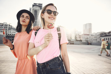 Portrait of positive woman putting hand on shoulder of cheerful girl. They walking along street and tasting delicious lollipops