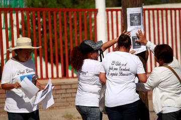 Activists and relatives of missing people posy pictures on a pole as they take part in a march to try to find their loved ones in the Valley of Juarez where they have found several bodies buried, on the outskirts of Ciudad Juarez